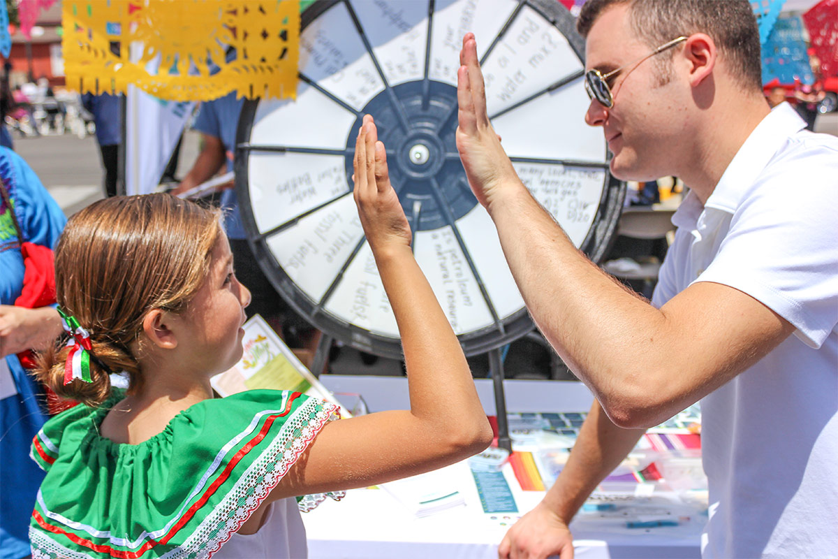 One of our CEI volunteers high-fives a young student after spinning the Careers in Energy prize wheel at the 2019 Santa Paula Cinco de Mayo Festival.